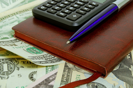 Still Life with cash dollars, notepad, calculator and pen.