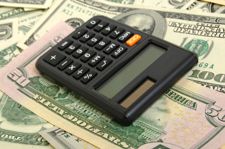 denominations: Still Life with a calculator and dollars in cash in various denominations.