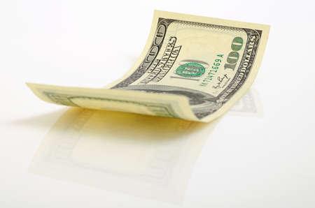 Gebogen honderd-dollarbiljet dicht omhoog op een licht vliegtuig. Stockfoto