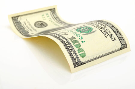 Curved hundred-dollar bill close up on a light plane. Reklamní fotografie