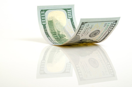 Gebogen honderd dollar bill close-up op een licht vliegtuig. Stockfoto