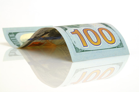 incentives: Curved hundred-dollar bill close up on a light plane. Stock Photo