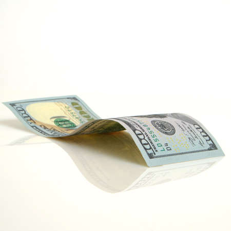 cashing: Curved hundred-dollar bill close up on a light plane. Stock Photo
