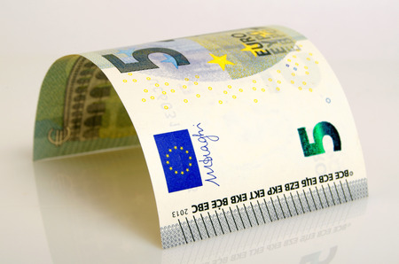 cashing: Five euros banknote closeup of on a light background. Stock Photo