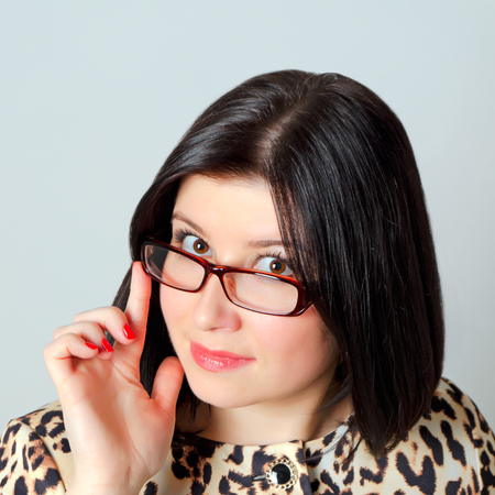 Groomed woman in glasses with instructing gesture.
