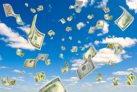 accrual: Money falling on the background sky.