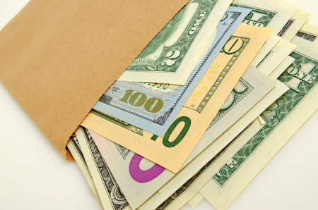 transfers: Cash dollars in paper envelope close-up.