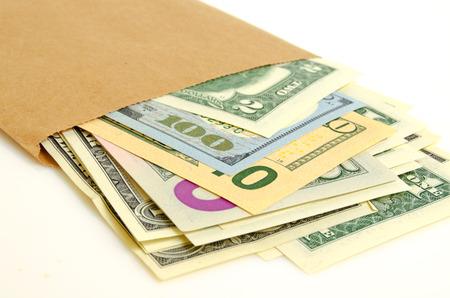 cashing: Cash dollars in paper envelope close-up.