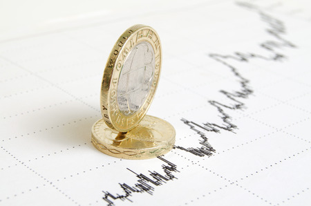 forecasts: British coins on the exchange chart.
