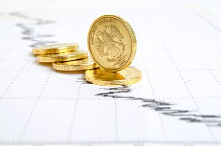 indices: Falling ruble still life with financial charts and coins.