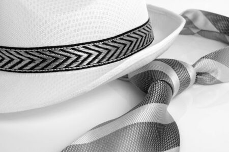 stillife: Hat and a tie with diagonal stripes on a light background. Stock Photo