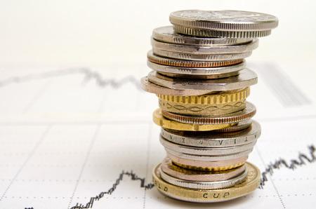 決算スケジュールに積み上げられた、さまざまな国からの硬貨。