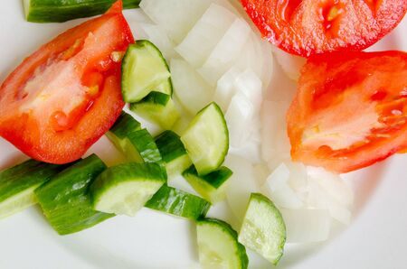stillife: Preparation of salad from fresh cucumbers and tomatoes.