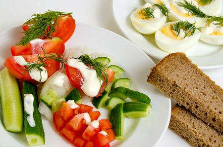 lunchbreak: Salad of tomatoes and cucumbers, eggs and bread on a light plane. Stock Photo