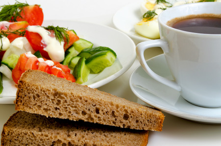 lunchbreak: Salad of tomatoes and cucumbers, eggs, bread and coffee. Stock Photo