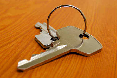 Bunch of keys on a wooden texture. Stock Photo