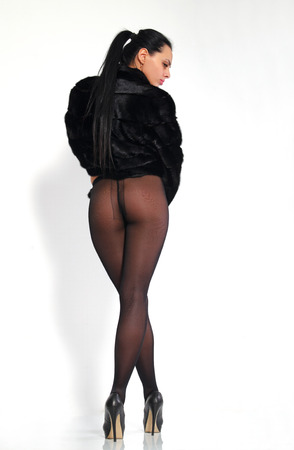 Beautiful, long-legged girl in pantyhose and a mink coat.