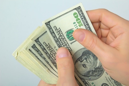 cashing: Cash US dollars in the hands on a light background. Stock Photo
