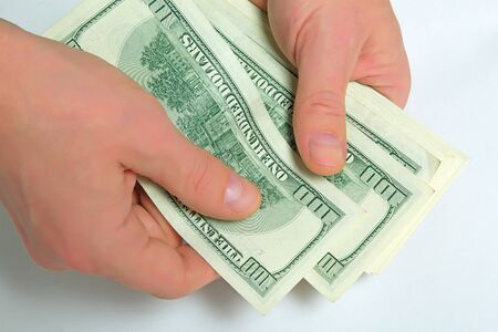 stimulus: Cash US dollars in the hands on a light background. Stock Photo