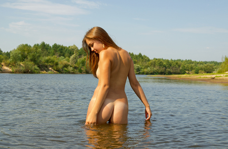 nude nature: Beautiful girl naked bathes in the river summer day.