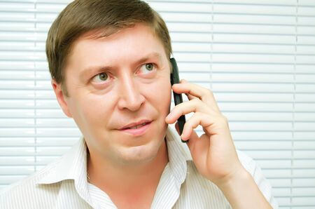 caller: Businessman talking on a cell phone. Stock Photo