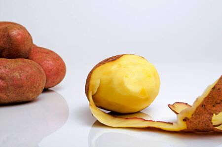 Clean the potato from the husk on a light background.