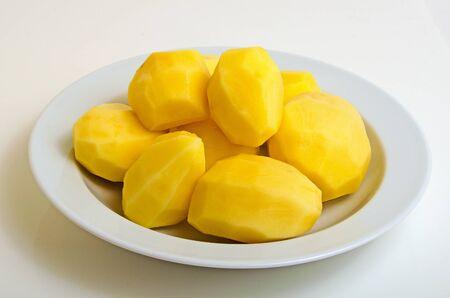 purified: Purified crude potato on a plate on a light background.