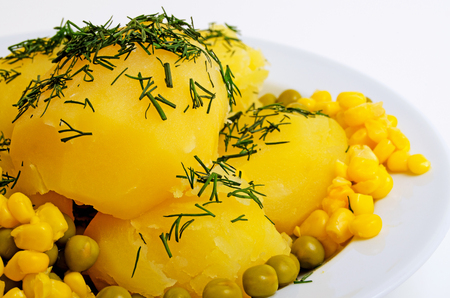 Boiled potatoes with green peas, corn and dill. Stock Photo