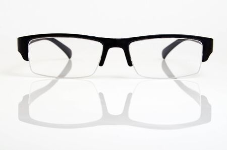 Glasses in a black plastic frame on a light background. Фото со стока - 74437627