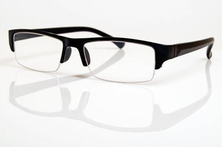 Glasses in a black plastic frame on a light background.