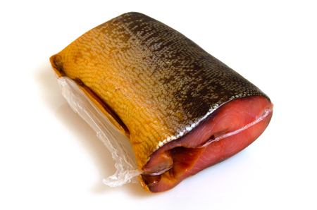 A piece of pink salmon smoked in a vacuum package against a light background.