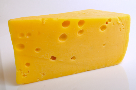 microelements: Sector of hard cheese on a light background close-up. Stock Photo