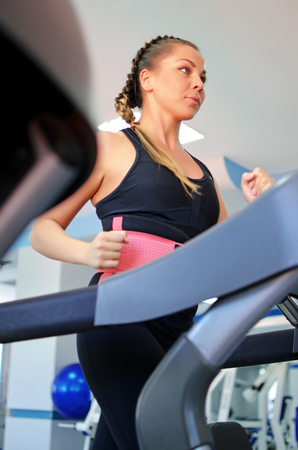 Young woman is running on a treadmill in the gym. Zdjęcie Seryjne