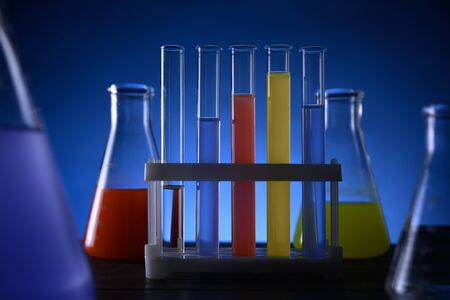 test tubes and flasks with colored liquids stand on a table