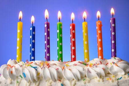 candele multicolori bruciano su una torta di compleanno su sfondo blu