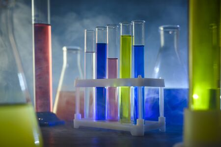 test tubes and flasks stand in the laboratory in a smoky background
