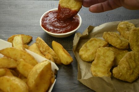 hand takes nuggets and dips it in sauce