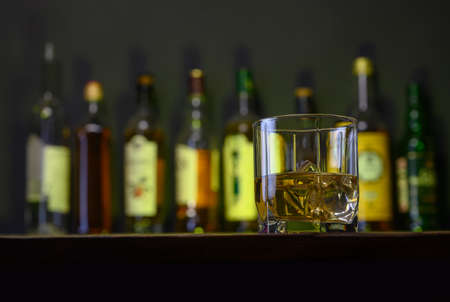 whiskey with ice stands on a wooden bar counter