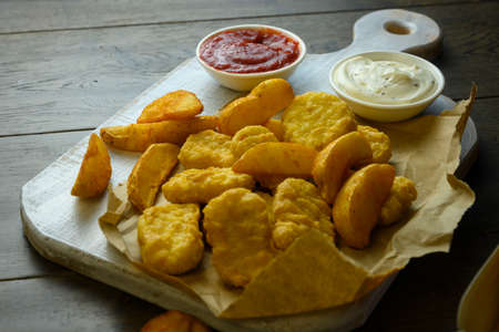on a white board are chicken nuggets and fried potatoes