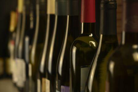 de nombreuses bouteilles de vin se tiennent dans une rangée