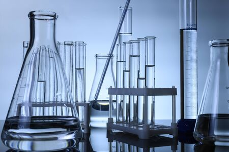 test tubes and flasks stand with clear liquids on a table