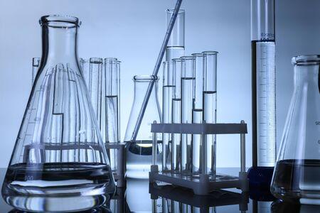 les tubes à essai et les flacons se tiennent avec des liquides clairs sur une table
