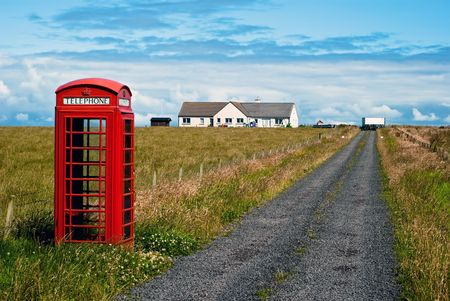 listeners: red phone booth standing alone in landscape