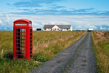 cabina telefonica: rojo cabina de tel�fono en pie por s� sola en el paisaje