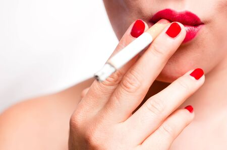 mouth with red lips and red finger nails smoking cigarette Stock Photo