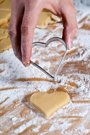 Heart shape is gouged in the dough by hand Stock Photo - 8063636