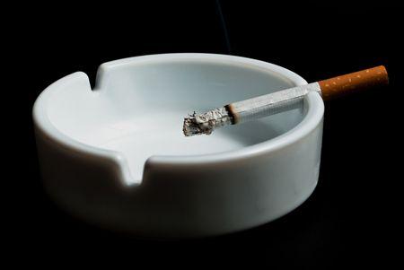 burning cigarette in the ashtray white on black background photo