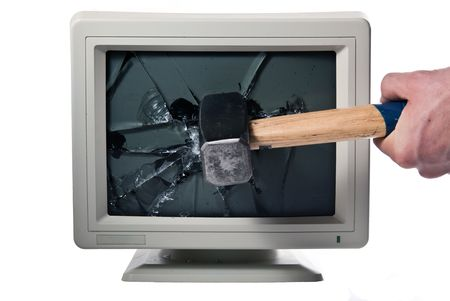 hit tech: vintage monitor is smashed with a hammer Stock Photo
