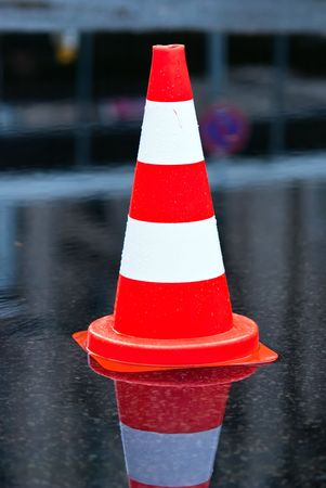 warning cone in a puddle at the street photo