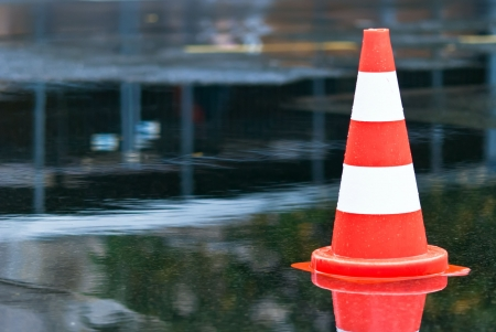 warning cone in a puddle at the street